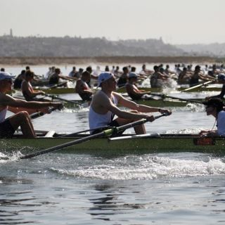 A Group Of People Rowing A Boat In The Water